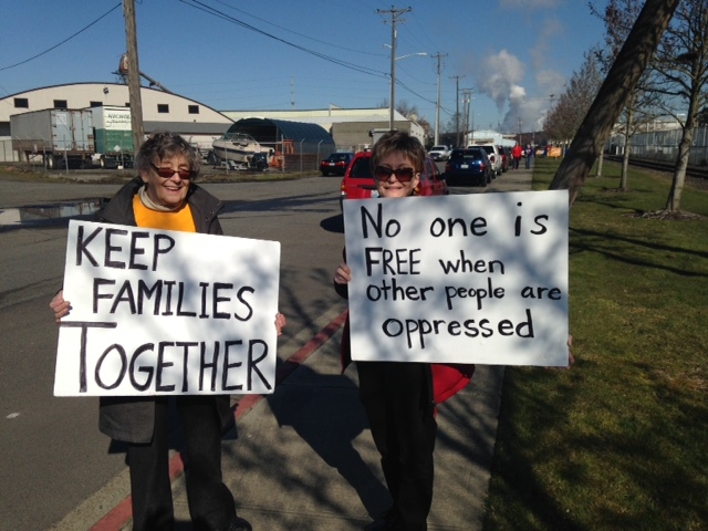 Two women holding signs at demonstration