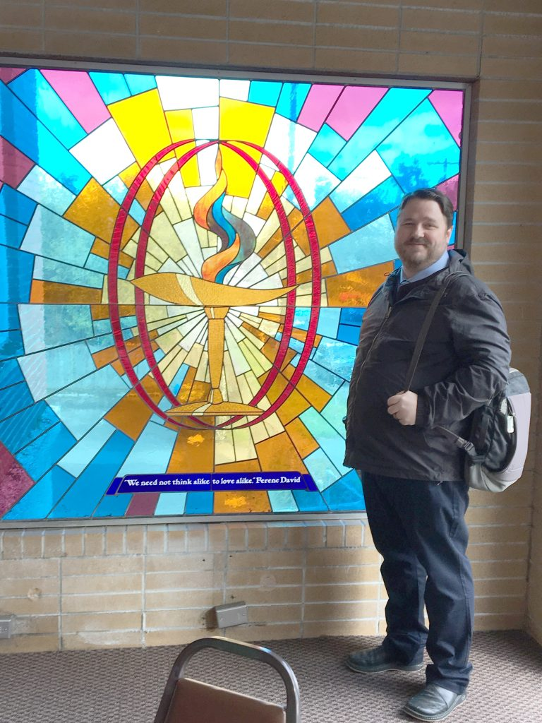 Rev. Christopher Wulff standing by stained glass window in narthex